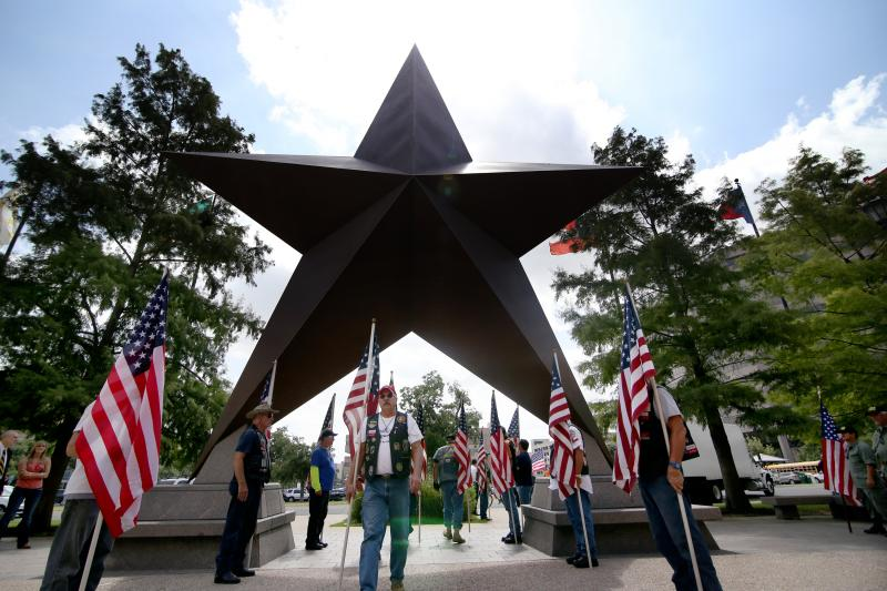 Patriot Guard Riders walk under the bronze star in the the Bullock Texas State History Museum's plaza.