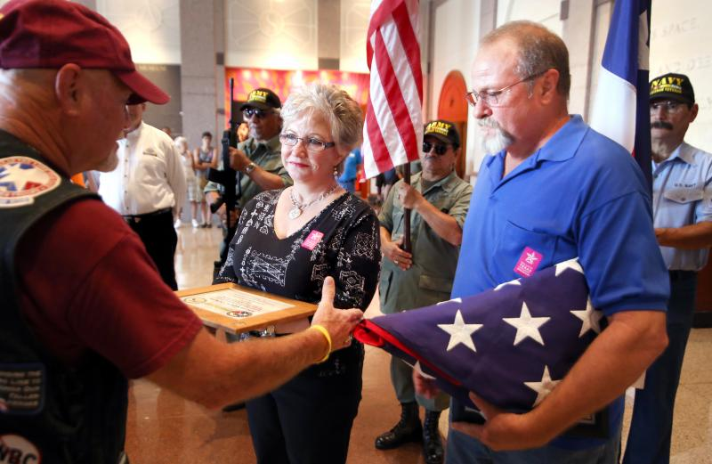 Patriot Guard Rider Cliff Jordan of Houston presents an American flag to Mrs. Linda Kaplon, widow of Cpl. Felix Kaplon, Jr., a Texas Soldier killed in Vietnam in 1968.