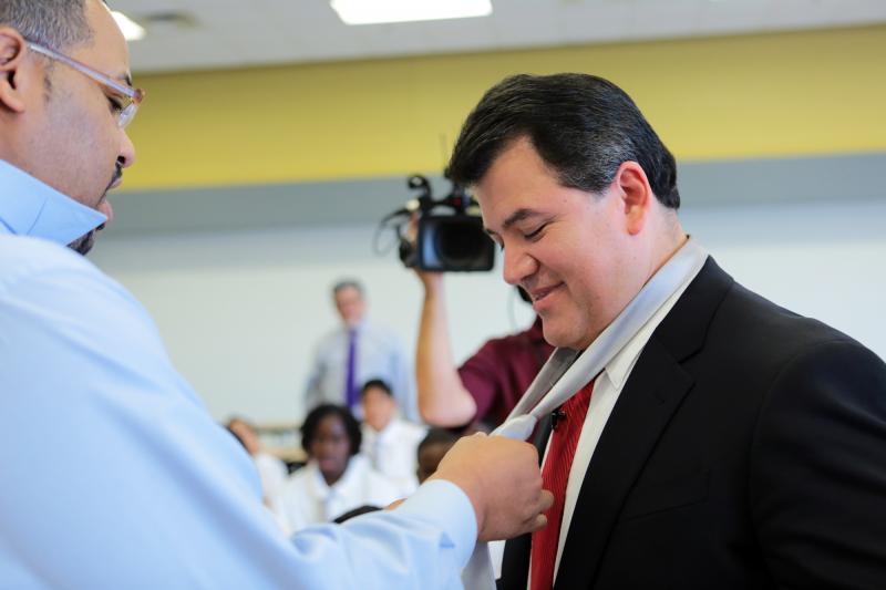 Principal Sterlin McGruder demonstrates the proper way to tie a windsor knot on Interim Superintendent Cruz.