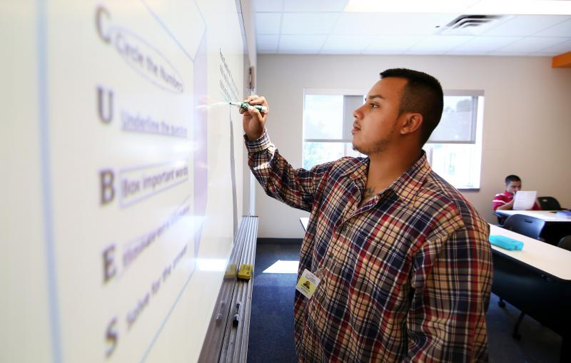 Armando Rodriguez completes a math problem at the Goodwill Excel Center. The school is the first free public charter school for adults ages 19-50 in Texas. It's goal is to provide adults the opportunity and support to earn a high school diploma and post-s