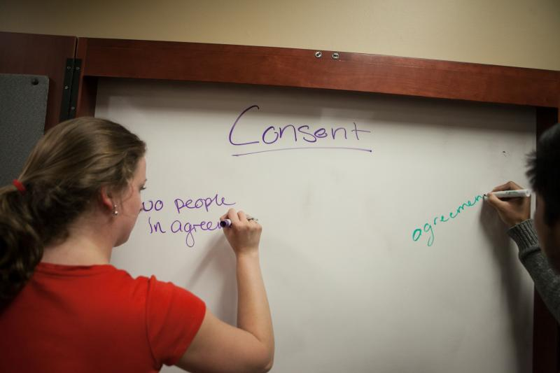 "In between acting, the performers list what consent means on a white board. The Voices Against Violence group reherses the skit ""Get Sexy, Get Consent."" The performers' friends were audience members, giving the actors a chance to practice with audience pa"