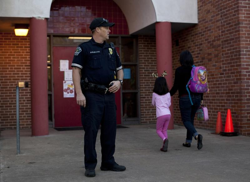 Austin Police Officer Cory Ehrler monitors the entrance to Ridgetop Elementary School after classes start on the Monday following the Sandy Hook Elementary School shooting.