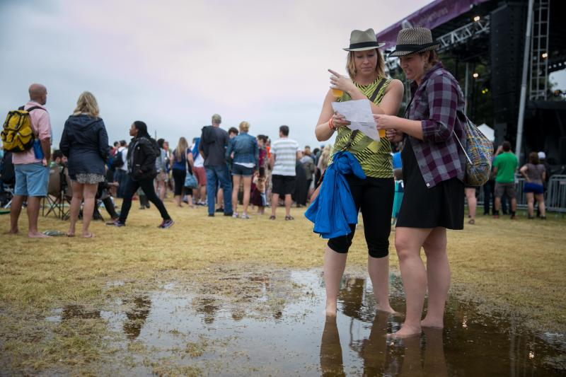 Two attendees weren't hampered by the second weekend's mud, as they try to find the next show to catch.