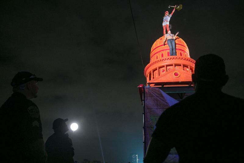 An unidentified festival goer stands atop the replica of the Texas State Capitol inside Zilker Park during ACL surrounded by police, emergency crews, and a large festival audience.