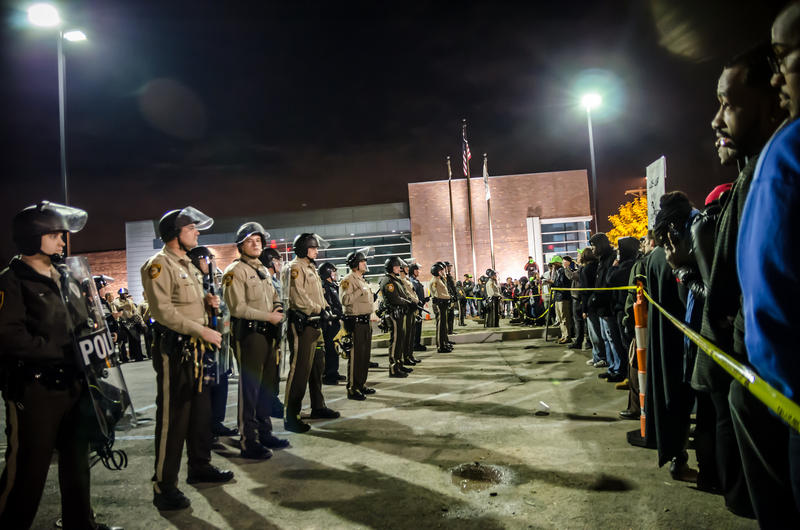 A vigil in support of Michael Brown occurs outside of the Ferguson Police Department. Ferguson police have been criticized for what some have called an overly miliarized response.