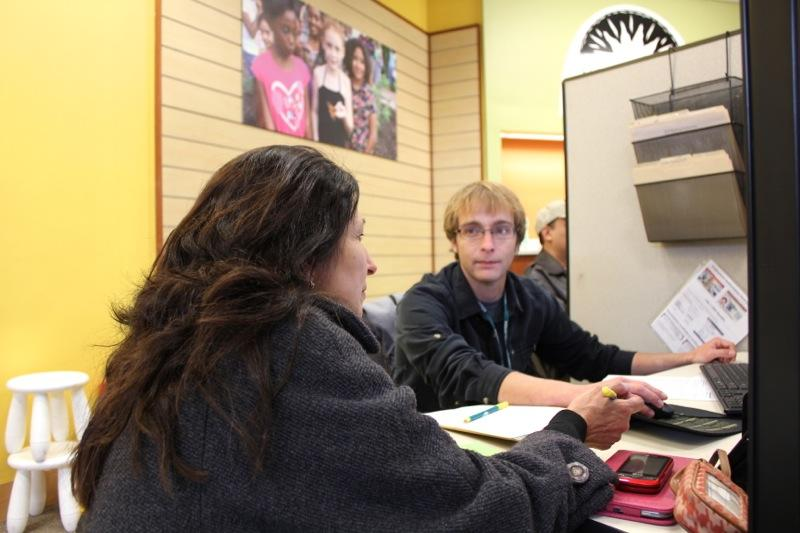 Adrian Zeh, right, helps a health insurance consumer at the Foundation Communities center inside Austin's Highland Mall on Nov. 14, 2014.