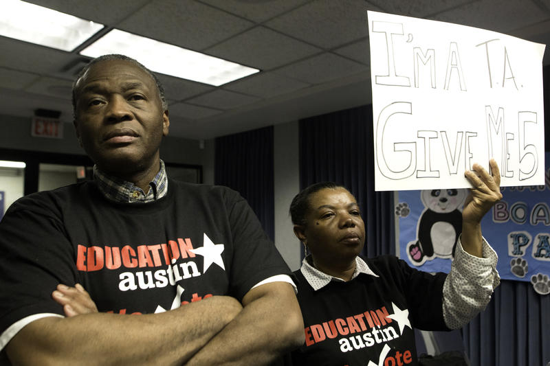 Francis and Patricia Garza hold up a sign requesting a 5% raise for AISD employees at the Board of Trustees meeting.