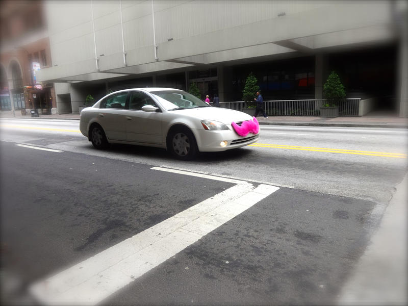 A Lyft car, complete with trademark pink mustache. Many of the fuzzy ones have been replaced with smaller glowing indoor mustaches.