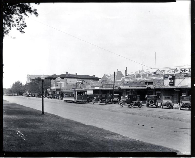 A photo of the Drag from 1927 showing the University Co-Op and a street car.