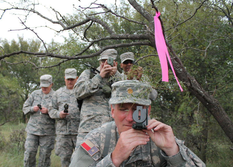 Maj. Gary Sherman, 3rd Battalion, 4th Regiment, Texas State Guard, uses a compass to determine his bearing during a Land Navigation joint training exercise in Henrietta, Texas, October 11, 2014.