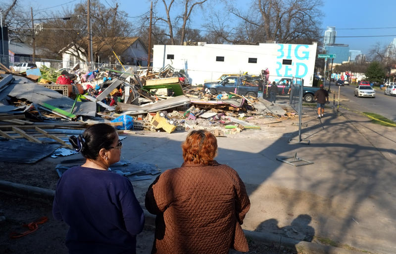 Jumpolin Rentals store owner Monica Lejarazul (right) and neighbor Diane Ontiberos (left) look on as a fence is erected around the remains of the storefront in February.
