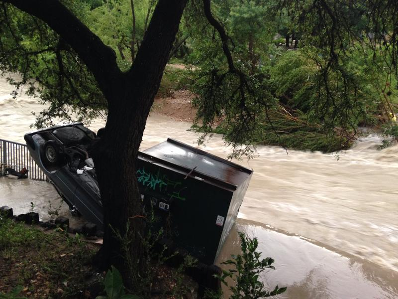 A car and dumpster on the side of Shoal Creek.