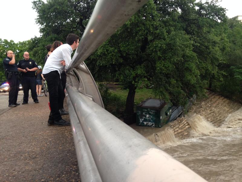 Onlookers watch a swollen Shoal Creek with APD officers nearby.