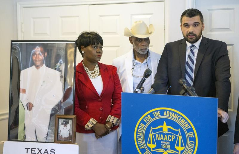 A photo of Danarian Hawkins is seen as his mother, Jacqueline Smith, Dr. James Douglas, and Amin Alehashem, address the media during a news conference, Wednesday, July 29, 2015, in Houston.