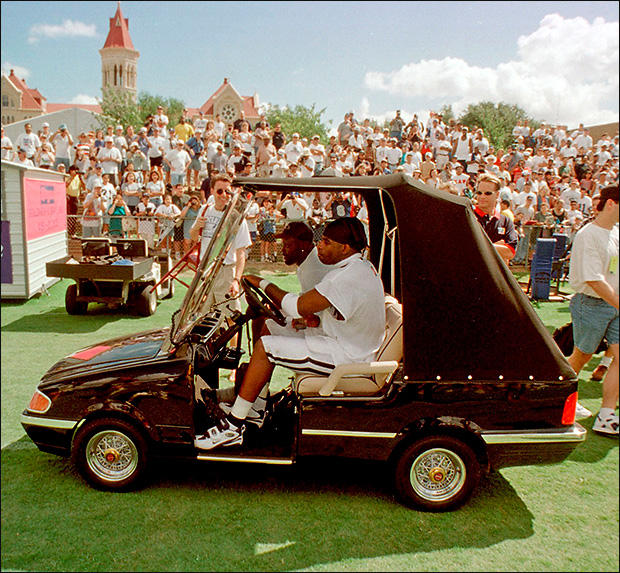 Then-Dallas Cowboy Deion Sanders takes a ride in a custom golf cart in front of St. Edward's main building.