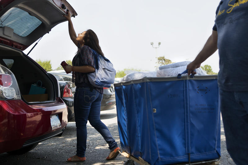 Erika Carbajal-Ramos finishes unloading her belongings from her family's car. Erika has started classes at Our Lady of the Lakes.