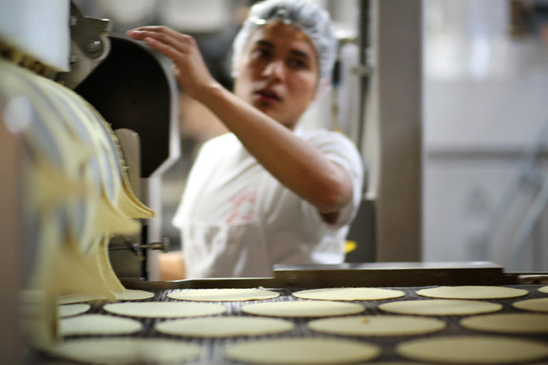 Tortillas made from corn masa flour move down a conveyer belt at the El Milagro plant in San Marcos, Texas.