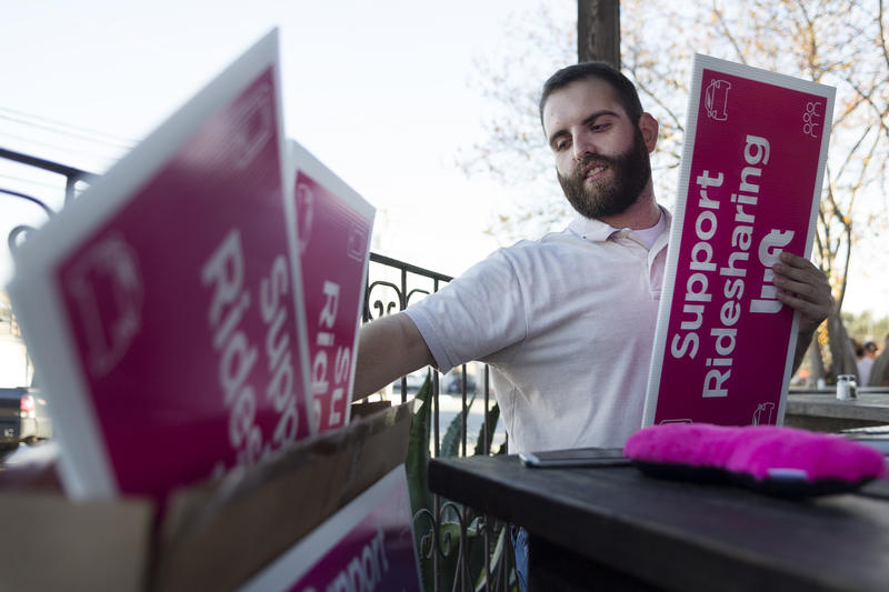 Skylar Buffington hands out signs in support of ridesharing at Austin Java on December 7, 2015. Buffington also works as a driver for Lyft.