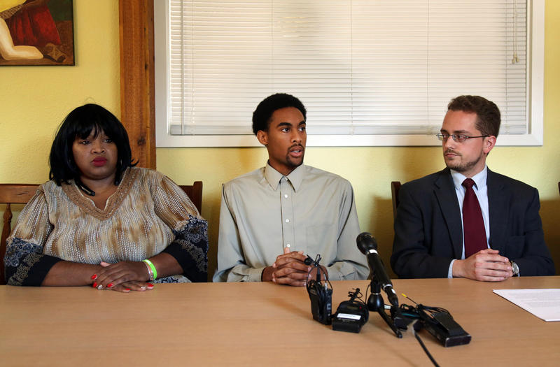 Plaintiff Jeremy King (center) speaks Monday at a press conference called by his attorney Brian McGiverin (right). King's mother Nevetta King (left) sat with her son.