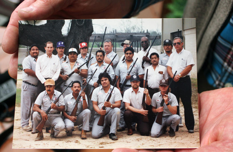 UT Austin's landscaping services manager John Burns holds up a photo of him (back row, second from left) and the team charged with controlling the campus grackles with blank-filled shotguns.