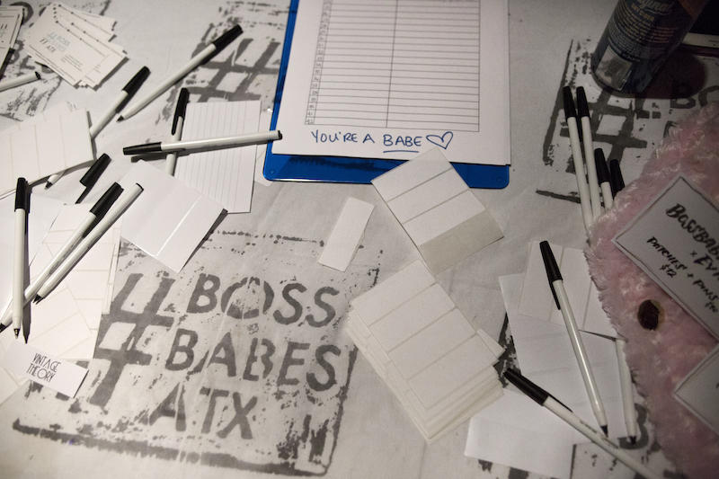 The Boss Babes ATX sign-in table is littered with name tags and notecards.