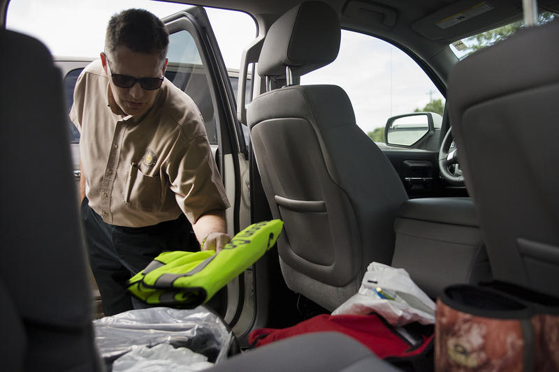 Williamson County Justice of the Peace Bill Gravell inspects his boots, reflective jacket and body bags, which he always keeps in his car in case he gets called out to a dead body.