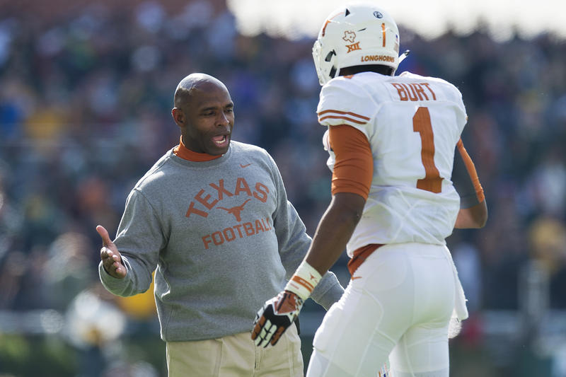 Texas football coach Charlie Strong celebrates with wide receiver John Burt during the Longhorns 23-17 win over Baylor in their 2015 finale.