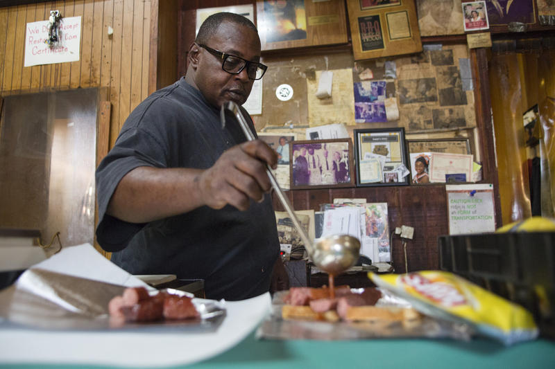 Brian Mays, owner of Sam's BBQ, ladles sauce on a customer's order. Mays says he's been offered to sell his property, but he's not selling.
