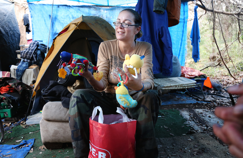 Courtney Meeks goes through baby toys at her campsite.