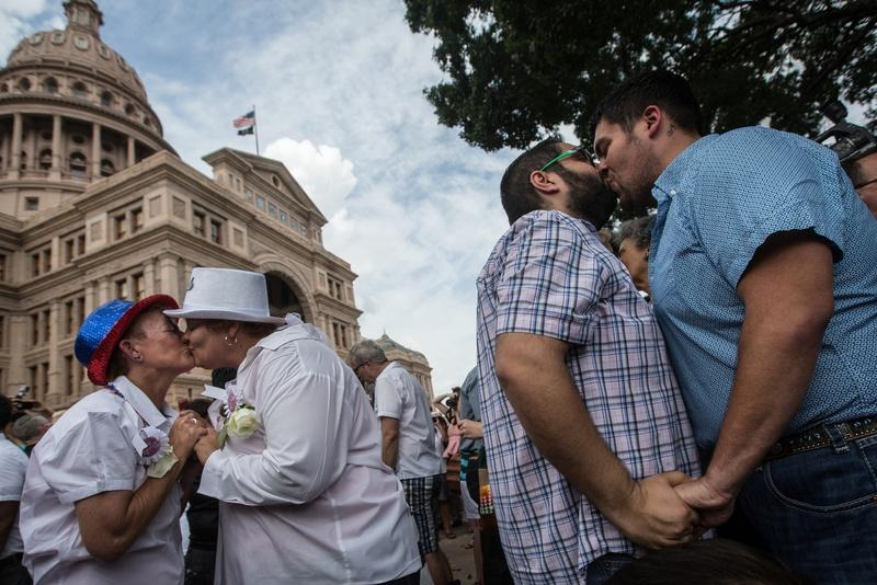 "Couples embrace at the conclusion of the ""Big Gay Wedding"" ceremony on the south lawn of the Texas Capitol on July 4 after the U.S. Supreme Court legalized same-sex marriage in June."