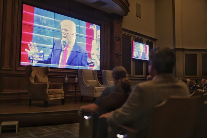 Attendees of a Texas Public Policy Foundation inaugural watch party watch as Donald Trump delivers his first speech as president of the United States.