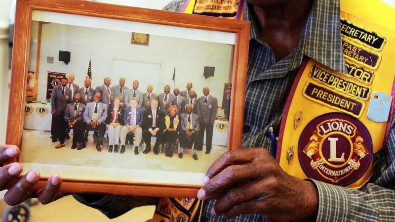 "Clarence McClure holds a picture of some of the original ""lions"" from Austin."