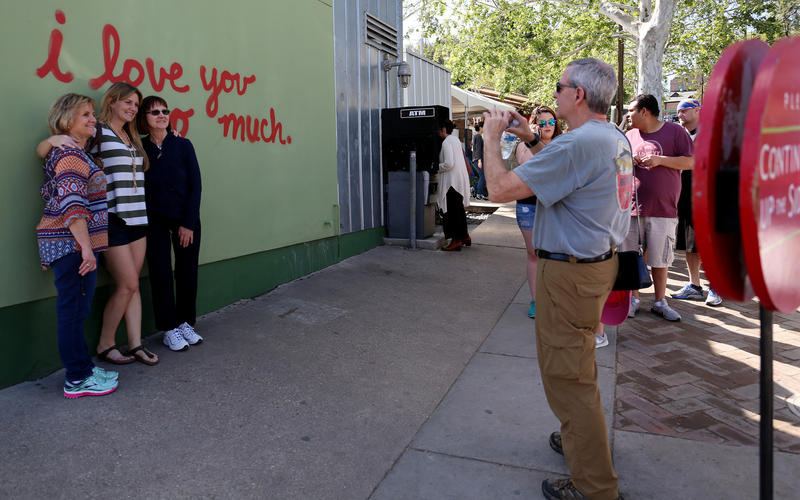 "A line forms around the ""I love you so much"" mural on South Congress Avenue during SXSW 2017."