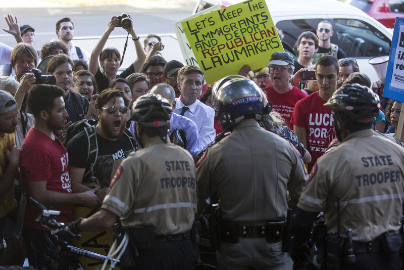 """Demonstrators outside the Office of the Governor support a sit-in protest led by City Council Member Greg Casar and dozens of others to protest Senate Bill 4, the so-called """"sanctuary cities"""" bill."""