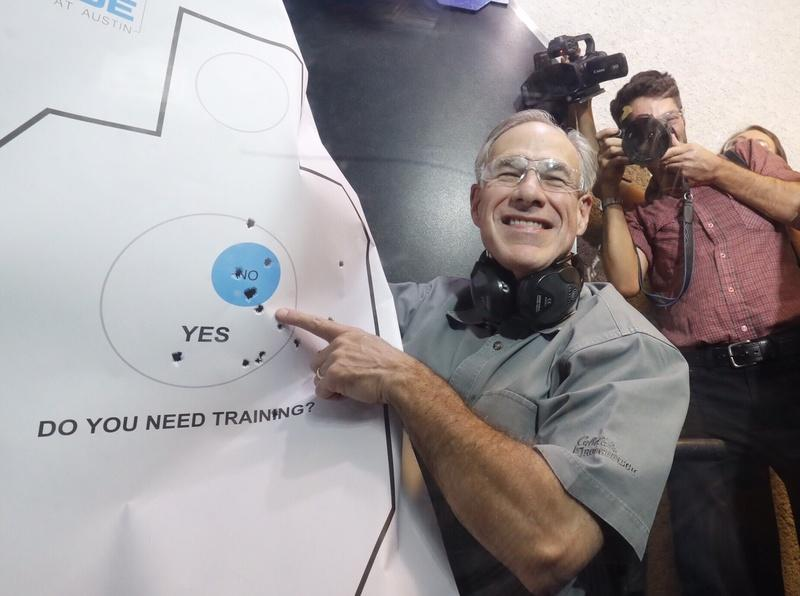 Gov. Abbott admires his practice target after signing Senate Bill 16, which reduces the first-time fee for a license to carry handguns Friday.