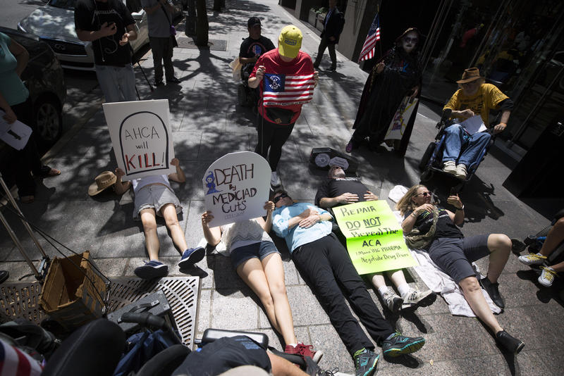 Protesters stage a die-in outside of Sen.  John Cornyn's office.