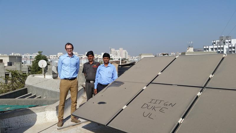 Duke Professor Mike Bergin (left), Chinmay Ghoroi (right), a professor at IIT Gandhinagar, and a member of the ITT staff stand near solar panels in Ahmedabad, India. The writing on the panel shows how dirty they are.