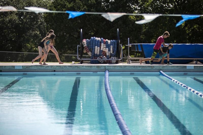 Swimmers await lessons as Paul Slutes and his crew work to fix an issue at Balcones Pool in North Austin.
