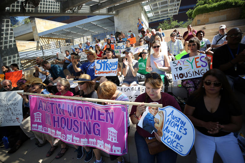 Activists and affordable housing residents gather outside City Hall on Saturday to speak against proposed cuts to the Department of Housing and Urban Development.
