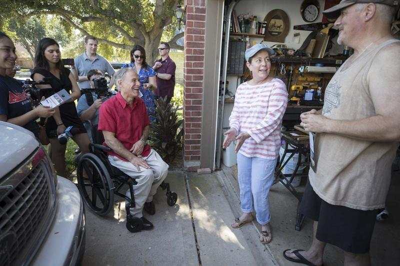 Texas Gov. Greg Abbott greets Wendy and Martin Randall during a block walk in North McAllen on Saturday, a day after he announced his bid for re-election.