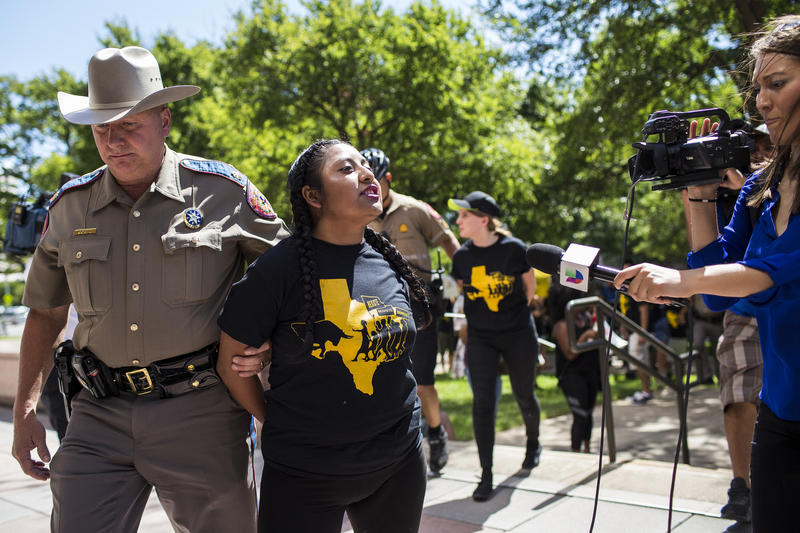 DACA recipient Catalina Santiago from Homestead, Fla., is arrested alongside fellow immigrants rights protesters outside the Texas State Capitol.