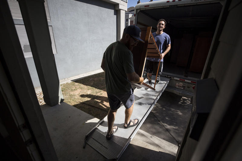 Jesse Gable and Connor Bowie move furniture into an apartment in West Campus on Monday.