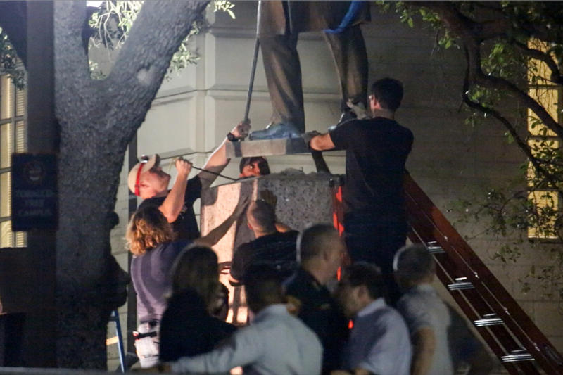 The statue of John H. Reagan, the postmaster general for the Confederacy, is taken down from the University of Texas at Austin campus. It was one of four statues removed overnight Sunday.
