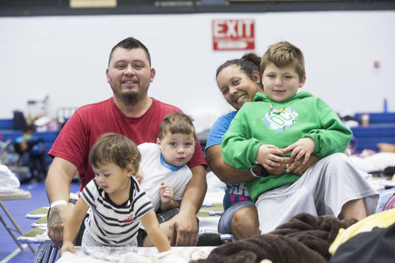 Larry Nash, Vanessa Dean and three of their four children - Legend, Lucas and Logan - at the Delco Center, which is providing shelter for Harvey evacuees. The family came to Austin from Nixon on Friday as the storm approached.