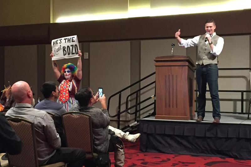 White nationalist Richard Spencer speaks while protester holds sign at Texas A&M campus in College Station on December 6, 2016.