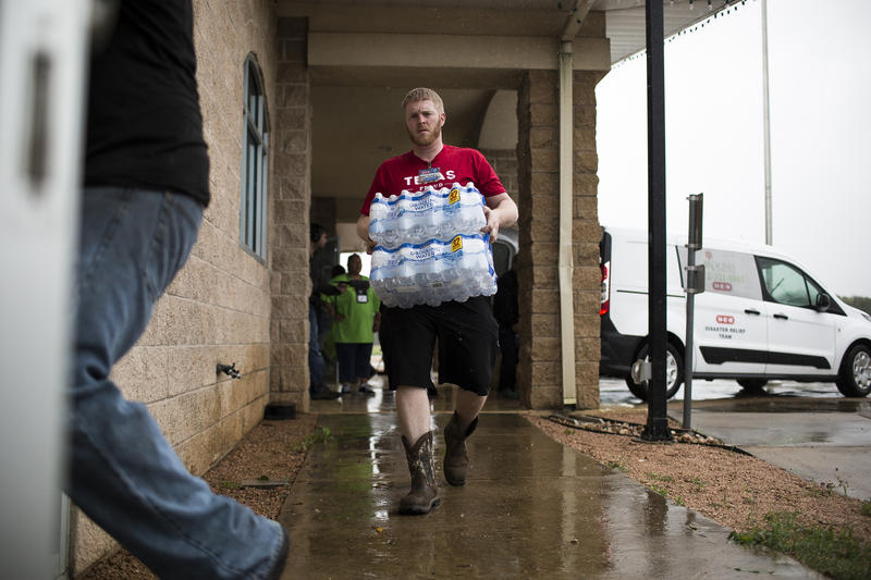 Volunteers with the HEB Disaster Relief Team bring supplies to the Smithville Recreation Center, which was serving as a shelter, on Sunday.