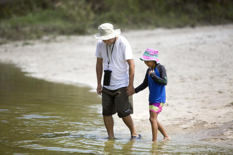 De Ding and his daughter, Kimmy, walk along the banks of Onion Creek. Ding and his family lived near the Barker Reservoir in Houston.