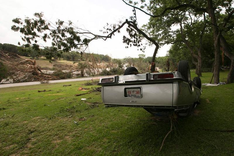 An overturned vehicle on the banks of the Blanco River that saw records breaking flood levels two days before, May 26, 2015.