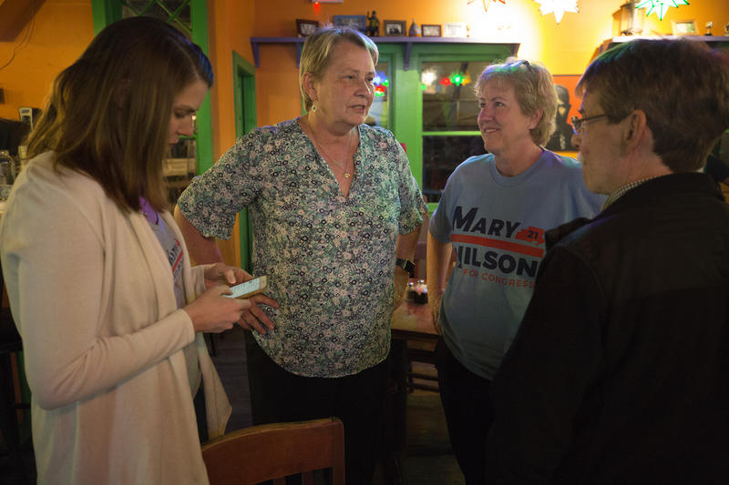 Mary Wilson, second from left, talks with supporters at an election watch party Tuesday at El Arroyo in West Austin. Wilson will compete in a runoff for the Democratic nomination for House District 21.