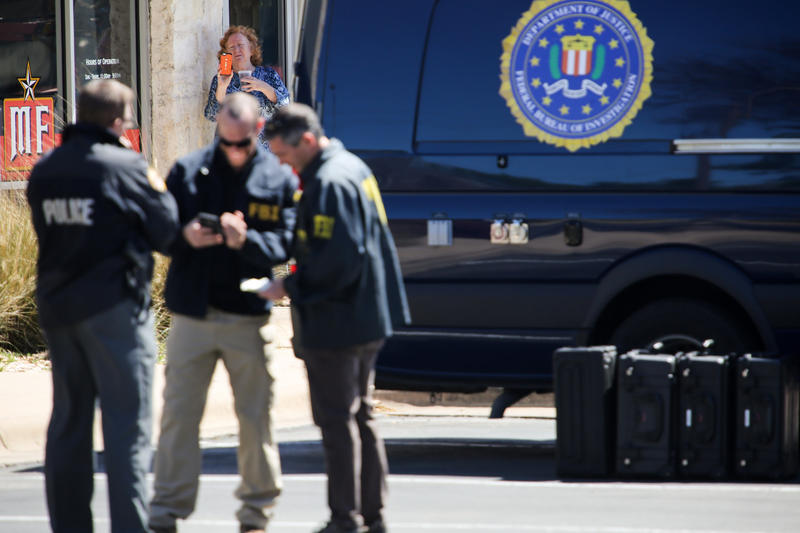 A woman records law enforcment officials outside the FedEx Office store in Sunset Valley on Tuesday. Officials say two package bombs were sent from the store.